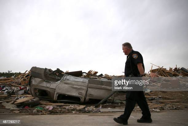 Police officer walks past an overturned car at a homesite that was destroyed by a tornado on Sunday, April 29, 2014 in Vilonia, Arkansas. After...