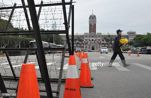 Police officer walks past barricades placed in front of the Presidential Palace in Taipei on March 21, 2014. Student protesters occupying Taiwan's...