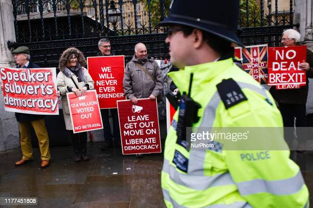 A police officer walks past proBrexit activists demonstrating outside the Houses of Parliament in London England on October 21 2019 House of Commons...