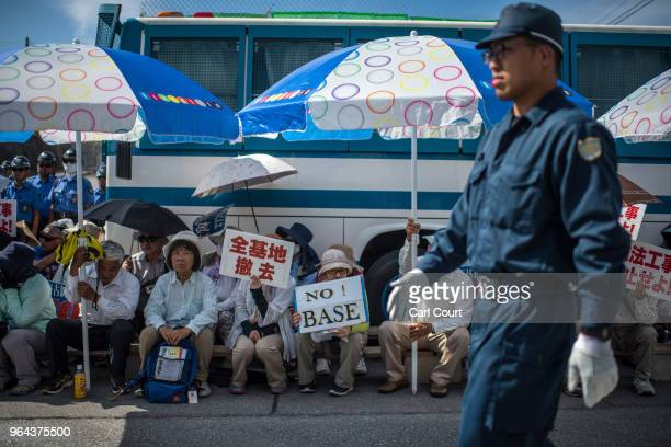 A police officer walks past protesters as they stage a sit in to block construction vehicles working on the expansion of Camp Schwab a United States...