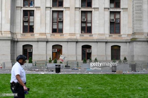 A police officer walks past the aftermath of a violent encounter between protestors and police officers at City Hall in Philadelphia PA on May 30...
