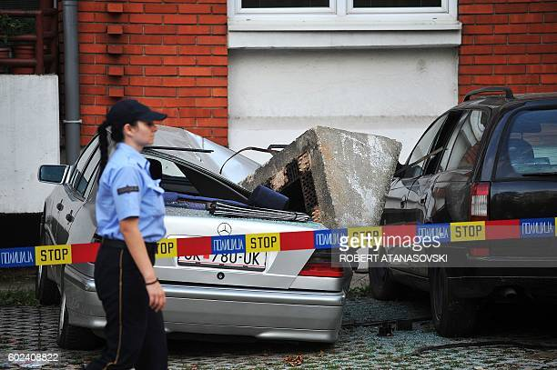 Police officer walks past the wreckage of a car after a chimney fell down near Skpoje, on September 11 following a moderate 5.3-magnitude earthquake,...
