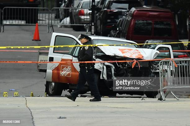 A police officer walks past the wreckage of a Home Depot pickup truck a day after it was used in an terror attack in New York on November 1 2017 The...