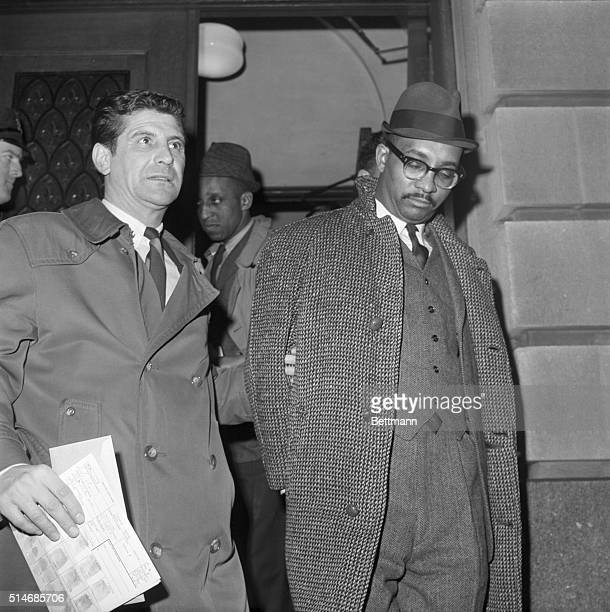 A police officer walks Reuben Francis Malcom X's secretary away from a jail in New York Francis is accused of shooting Thomas Hagen Malcolm X's...