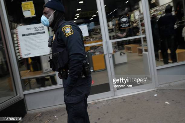 Police officer walks through downtown Newark as the city experiences a rise in Covid-19 cases on November 25, 2020 in Newark, New Jersey. Newark...
