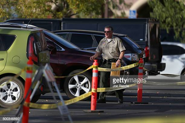 A police officer walks through the parking lot as law enforcement officers investigate the scene in the building at the Inland Regional Center were...