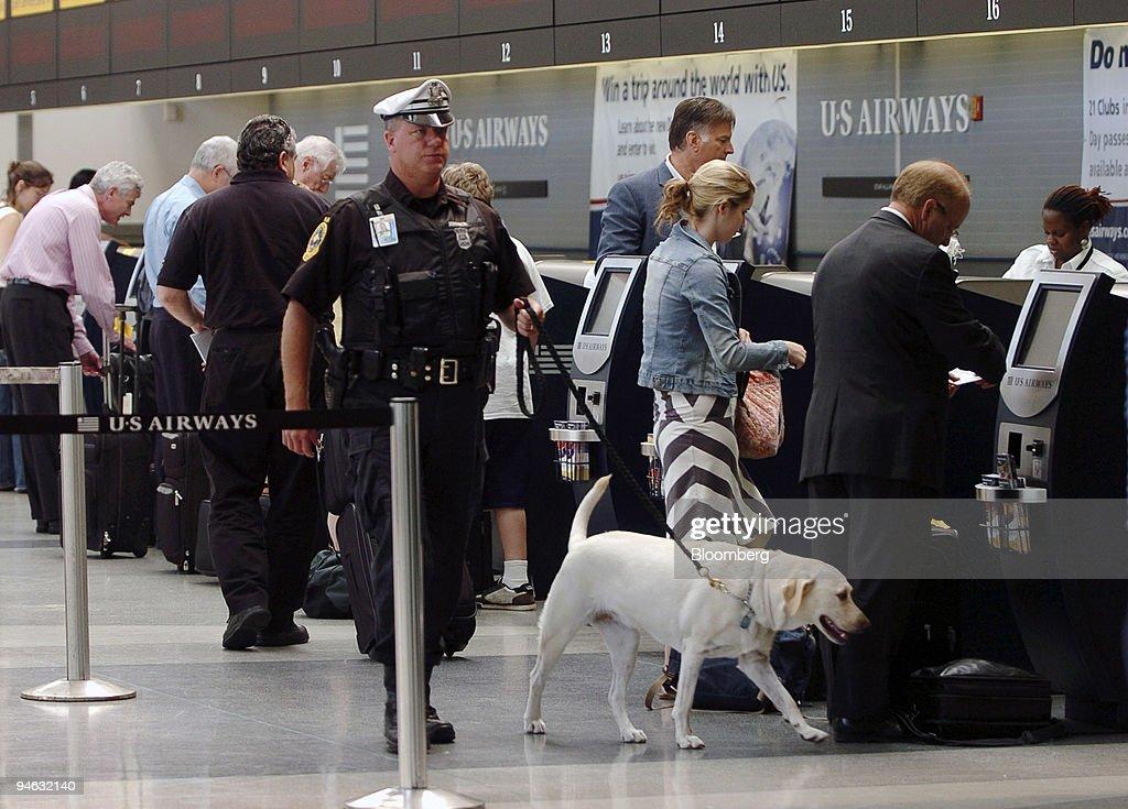 A K-9 police officer walks through the US Airways terminal a : News Photo