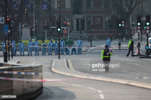 A police officer walks with floral tributes towards Westminster Bridge as police officers in forensics suits work in Parliament Square following...