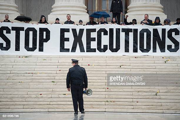 A police officer warns activists to leave during an anti death penalty protest in front of the US Supreme Court January 17 2017 in Washington DC /...