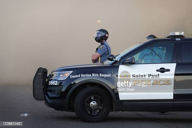 Police officer watches a retail store burn during a protest on May 28, 2020 in St. Paul, Minnesota. Today marks the third day of ongoing protests...