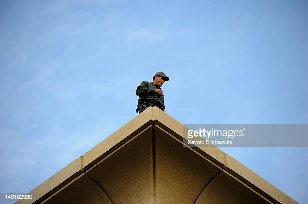 A police officer watches from the rooftop of the Aurora Municipal Center building as a crowd of thousands gathered for a prayer vigil for the victims...