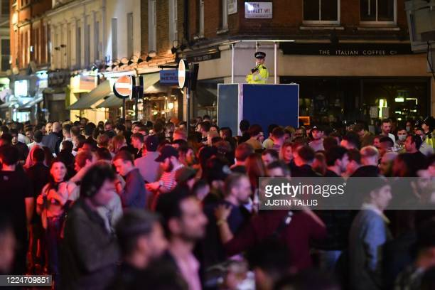 A police officer watches on from an elevated position as revellers drink in the street outside the bars in the Soho area of London on July 4 as...