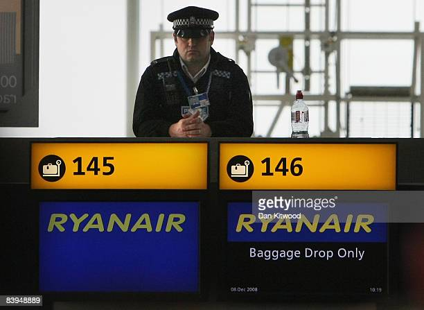 A police officer watches over passengers waiting for flight information in Stansted's main terminal after protesters caused major delays by occupying...