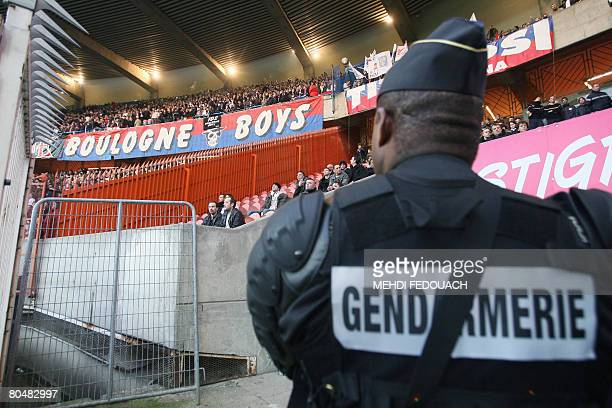 A police officer watches supporters of the Boulogne side at the ParcdesPrince stadium as part of security measures on April 2 in Paris prior to the...