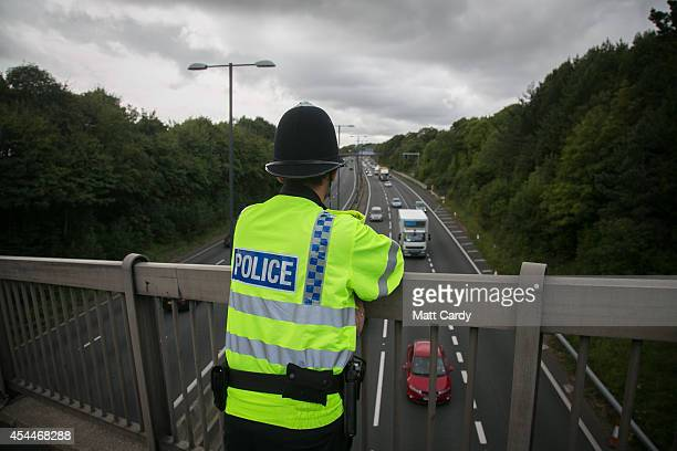 A police officer watches the M4 motorway running near the Celtic Manor Resort ahead of the Nato Summit 2014 that is being held in South Wales this...
