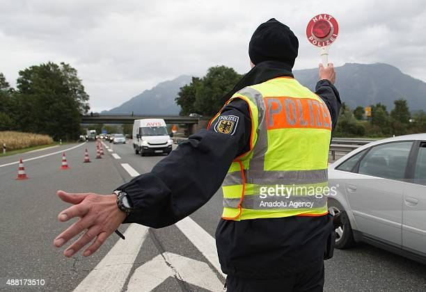 A police officer waves a car out of traffic for inspection at the German Austrian border on September 14 2015 near Bad Reichenhall Germany Germany...