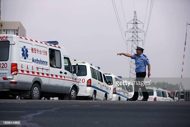 A police officer waves to an ambulance outside Baoyuan poultry plant at Dehui northeast China's Jilin province on June 3 2013 At least 119 people...