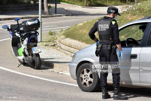 A police officer wearing a face mask and gloves as a preventive measure stops a driver at a checkpoint to ensure compliance with the rules during the...