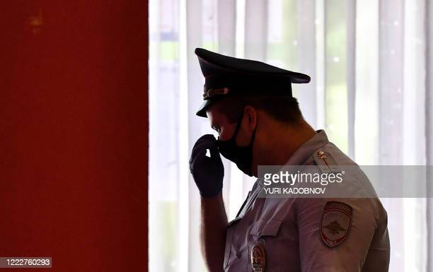 Police officer wearing a face mask and gloves is seen at a polling station in Moscow on June 25, 2020. - Russians were casting early ballots on June...