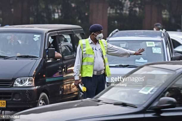 A police officer wearing a face mask directs traffic at an intersection in New Delhi India on Friday Nov 10 2017 Thick toxic smog enveloped New Delhi...