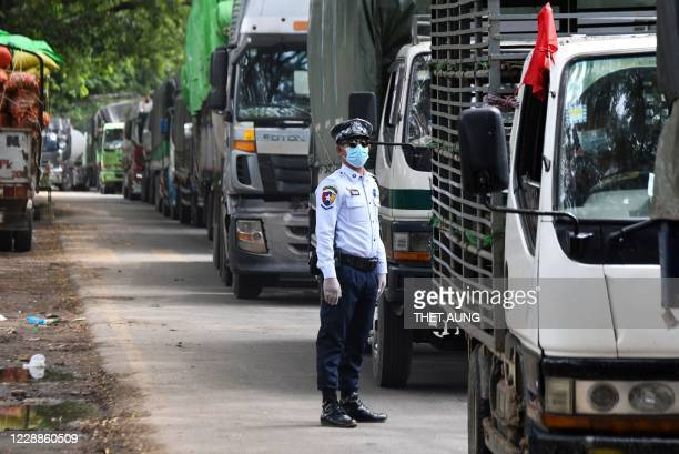 Police officer wearing a face mask stands beside rows of trucks at a health checkpoint, along Yangon-Mandalay highway near Naypyidaw to inspect...