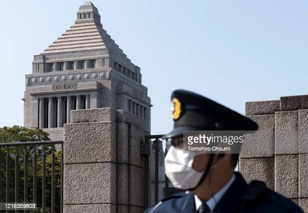 Police officer wearing a face mask stands in front of the National Diet building on April 02 in Tokyo, Japan. Japan's Prime Minister Shinzo Abe...