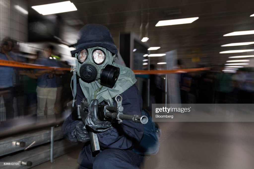 A police officer wearing a gas mask aims his weapon during an anti-terror drill on the sidelines of the Ulchi Freedom Guardian (UFG) military exercises at a subway station in Seoul, South Korea, on Tuesday, Aug. 22, 2017. North Korea warned the U.S. on Tuesday it will face 'merciless revenge' for ignoring Pyongyangs warnings over annual military drills with South Korea. Photographer: SeongJoon Cho/Bloomberg via Getty Images