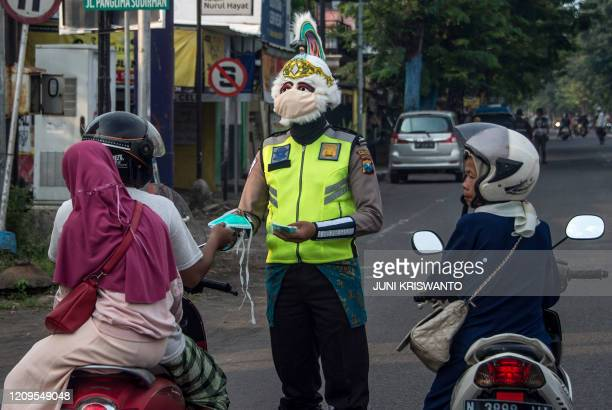 Police officer wearing a Indonesian a superhero costume on the street gives face masks to motorists in Pasuruan, East Java on April 9 amid concert to...