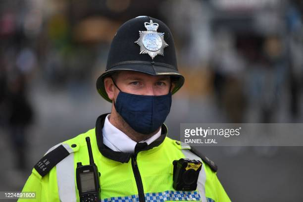 Police officer wearing a protective face covering patrols in Soho in London on July 5 as the Soho area embraces pedestrianisation in line with an...