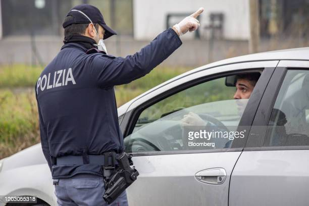 A police officer wearing a protective face mask speaks with a motorist at a yellow zone quarantine roadblock near the quarantine red zone in the town...