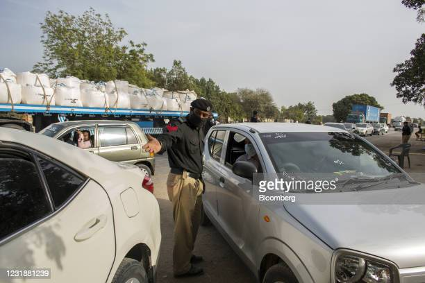 Police officer wearing a protective mask directs drivers travelling along a highway in the Matiari district of Sindh province, Pakistan, on...