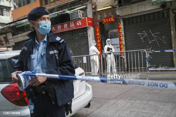 Police officer wearing a protective mask put up cordon tape outside an area under lockdown in the Jordan area of Hong Kong, China, on Saturday, Jan....
