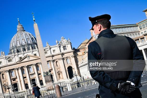 A police officer wearing a protective mask stands guard at the Vatican's Saint Peter's Square and its main basilica on March 11 2020 a day after they...
