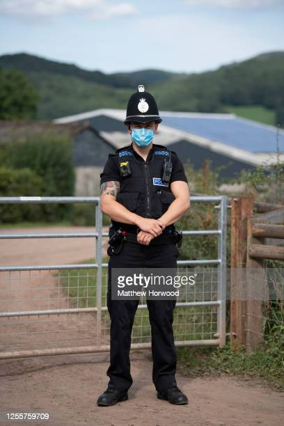 Police officer wearing a surgical face mask stands at the entrance to AS Green and Co farm on July 12, 2020 in Mathon, Herefordshire. AS Green and...