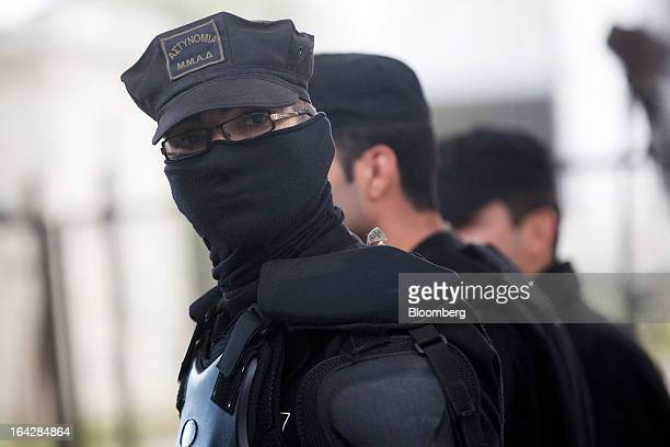 A police officer wearing body armour protects his face during a sandstorm while standing outside the Cypriot parliament in Nicosia Cyprus on Friday...