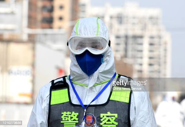 A police officer wearing protective mask and suit is on duty during disinfection work at Huanan Wholesale Seafood Market on March 4 2020 in Wuhan...