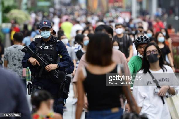 Police officer wearing protective mask patrols along the Orchard Road shopping belt on December 24, 2020 in Singapore. As Singapore prepares to...