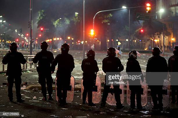 Police officer wearing riot gear work on controling Argentine soccer fans that became violent near the Obelisco de Buenos Aires after their team lost...