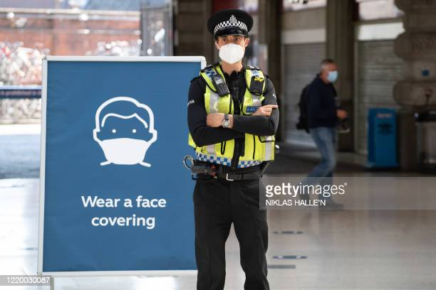 Police officer wears a face mask as he stands on the concourse at Waterloo Station in London on June 15, 2020 after new rules make wearing face...