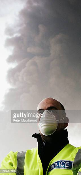 A police officer wears a face mask at a roadblock near a fire at the Buncefield fuel depot on December 11 2005 in Hemel Hemstead England The...