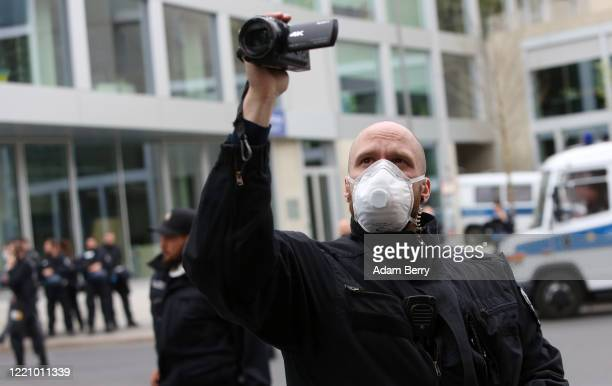 Police officer wears a face mask while monitoring a demonstration against restrictions on public life designed to stem the spread of the coronavirus,...