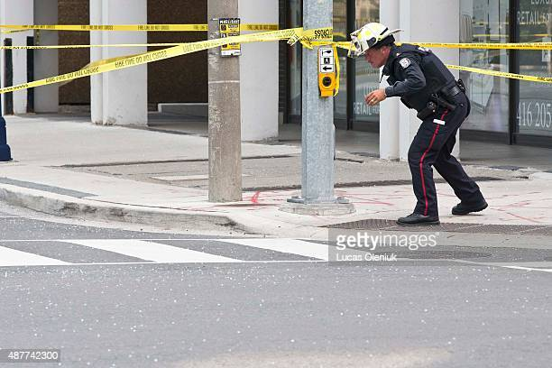 A police officer wears a fireman's helmet for protection after a broken pane of glass rained down on Bay Street and Yorkville Avenue Thursday...
