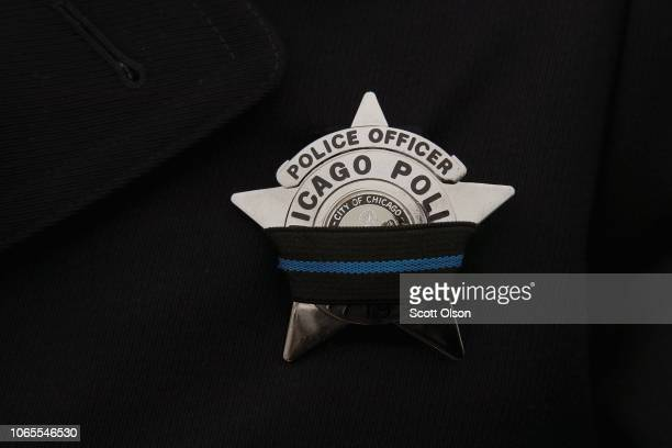 A police officer wears a mourning band on his badge as his department mourns Chicago Police Officer Samuel Jimenez during his graveside service at...