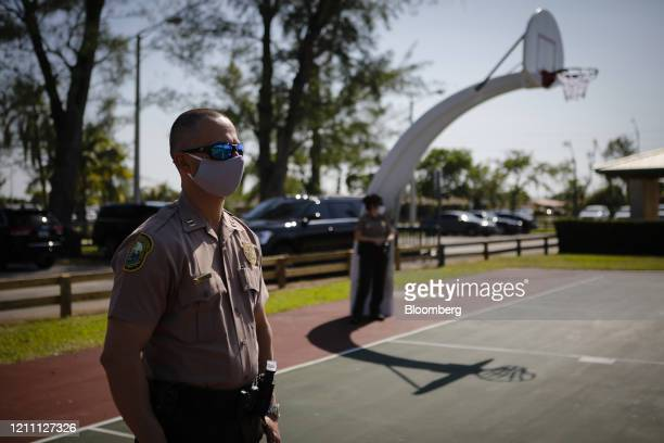 Police officer wears a protective mask while listening to Carlos Gimenez, mayor of Miami-Dade County, not pictured, speak during a news conference in...