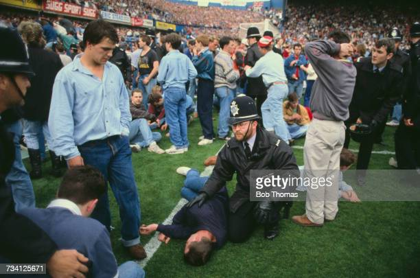 A police officer with a casualty on the pitch at Hillsborough football stadium in Sheffield after a human crush at an FA Cup semifinal game between...