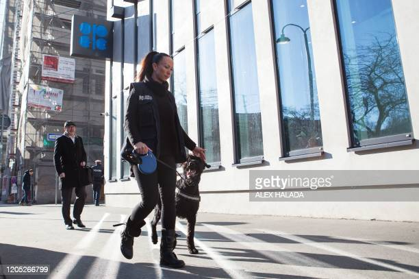 A Police officer with a dog patrols in front of the OPEC building in Vienna ahead of the 178th Organization of Petroleum Exporting Countries meeting...