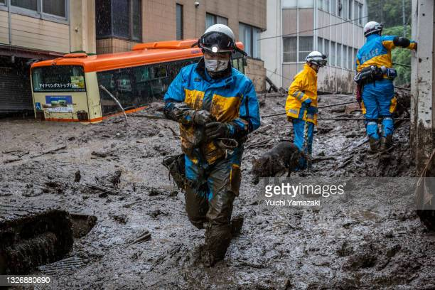 Police officer with a search and rescue dog, searches the area around the site of a landslide on July 04, 2021 in Atami, Shizuoka, Japan. Torrential...