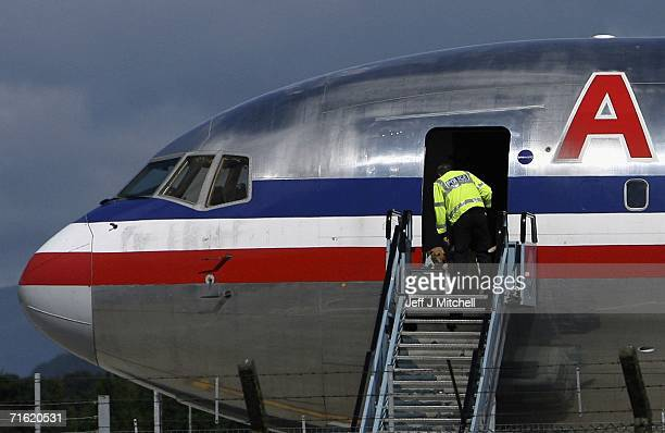 A police officer with a sniffer dog boards an American Airlines plane at Glasgow Airport August 10 2006 Glasgow in Scotland British Airports have...