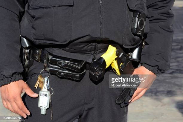 A police officer with a taser gun on his duty belt stands in the plaza in front of The Alamo in San Antonio Texas