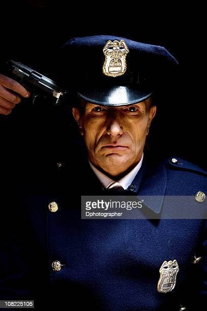 Oficial de policía con arma en contra de la cabeza, bajo llave